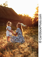 Happy and loving family in nature. Emotional and cheerful young blonde mother with her little laughing little daughter watching the rainbow sitting. Summer fun.