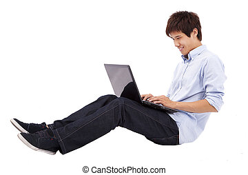Happy and relax young man using laptop on the floor isolated on white background