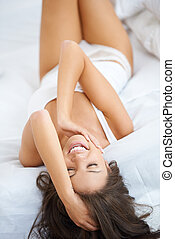 Happy and relaxed young woman on bed