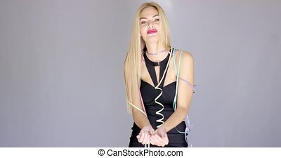 Happy and sexy young woman in evening dress dancing