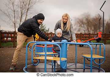 Happy and smiling family couple with little son riding on the carousel