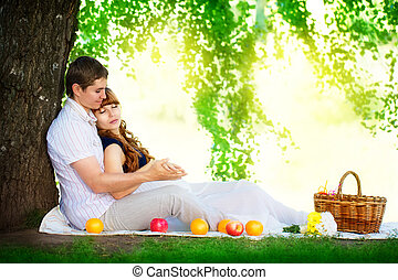 Happy and young pregnant couple hugging in nature enjoying summe