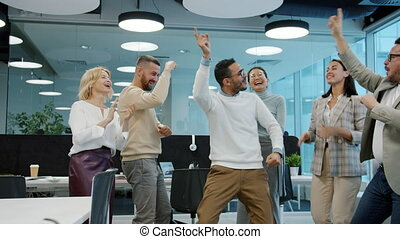 Happy Arab man dancing with multi-ethnic froup of colleagues in shared office during corporate celebration. Cheerful people, relaxation and events concept.
