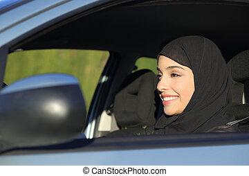 Happy arab saudi woman driving a car