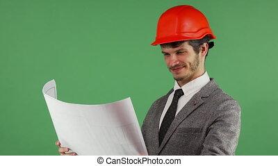Happy architect examining his blueprints smiling joyfully