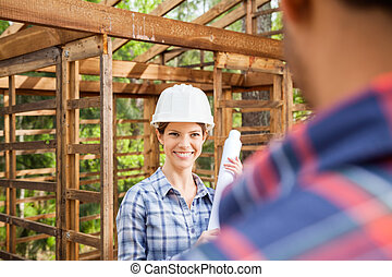 Happy Architect Looking At Colleague On Construction Site