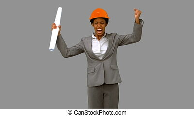 Happy architect raising arms on gre