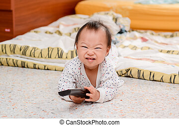 Happy Asian baby with television's remote control.
