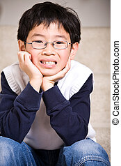 A shot of a hapy asian boy sitting