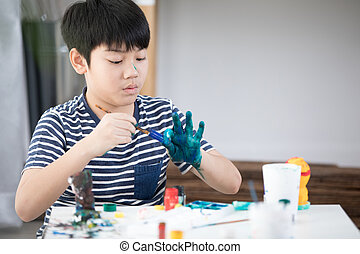 Happy asian boy painting paint.