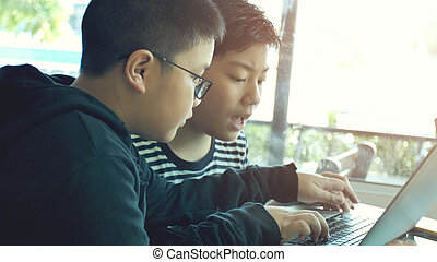 Happy asian boy typing on laptop computer.