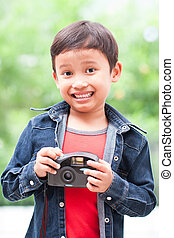 asian boy using a compact camera
