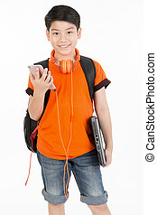 Happy asian boy using cellphone and holding laptop .