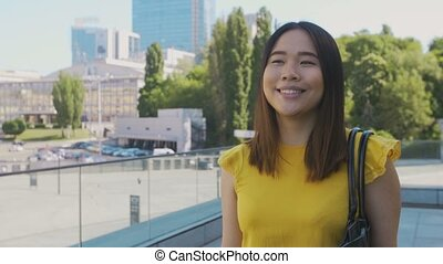 Happy asian business girl smiling while walking