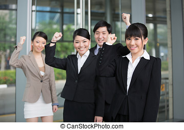 Happy Asian business team standing together with there...