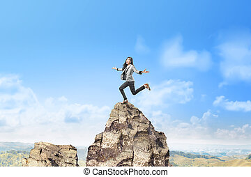Happy asian business woman jumping on top of the mountain