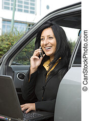 happy asian business woman sitting in her car and chatting...