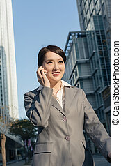 Happy Asian business woman talking on phone and walking on street in modern city, Taipei, Taiwan, Asia.