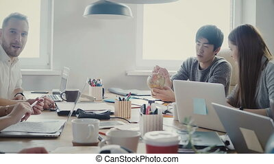 Happy Asian businessman takes a little globe, points at country at multiethnic office meeting in light loft coworking