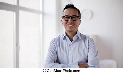 happy asian businessman waving hand at office