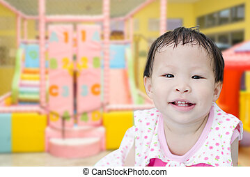 happy Asian child in a domestic sports room.