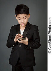 Happy asian child in black suit holding digital cell phone