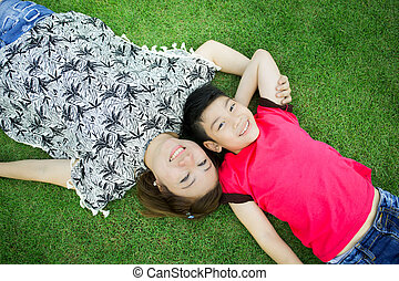 Happy asian child with mother play outdoors in the park