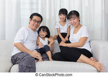 Happy Asian Chinese family sitting on the couch at home