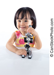 Happy Asian Chinese little girl with microscope