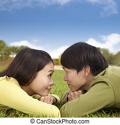Happy asian couple lying on the grass with cloud background