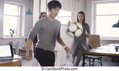 Happy Asian employee juggling football in office. Smiling...