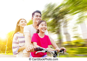 Happy asian family having fun in park with bicycle