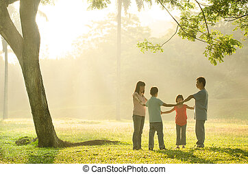 happy asian family having quality time playing in the outdoor green park during a beautiful sunrise