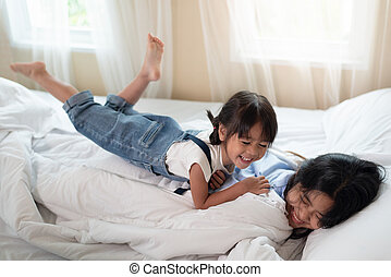 Happy Asian family loving children, kid and her sister relaxing together in bed