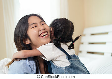 Happy Asian family loving children, kid hugging her sister, relaxing together in bed