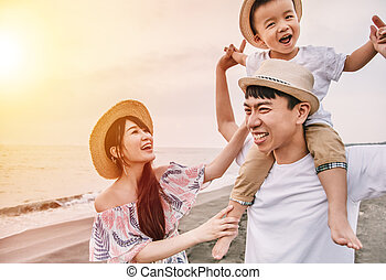 happy asian family playing on the beach at sunset