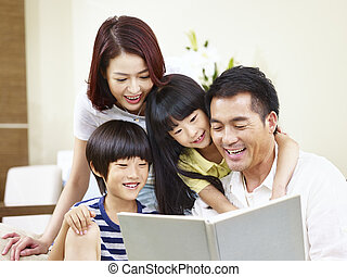 happy asian family reading a book at home