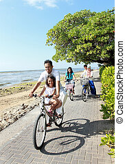 Happy asian family riding bikes in the beautiful morning at the beach. Outdoor portrait