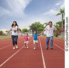 happy asian family running together on the Stadium track
