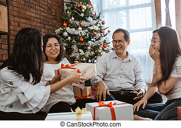 asian family sitting on the floor with gift box present
