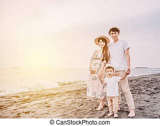 happy asian family standing on the beach at sunset
