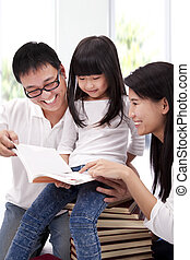 Happy asian family studing together. Parent helping daughter  reading book