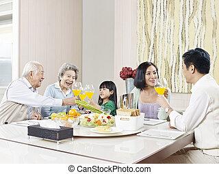happy asian family - three-generation family having meal at...