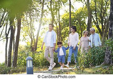 happy asian family walking in park