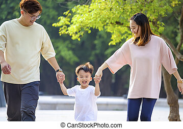 happy asian family  walking  in the park