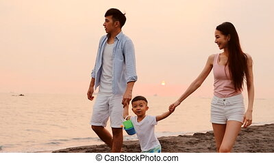 happy asian family walking on beach