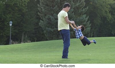 Happy asian father spinning his cute son on meadow