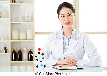 Happy asian female scientist with crossed arms in the laboratory