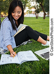 Happy asian female student in striped shirt writing to notebook, while studying in park, outdoor