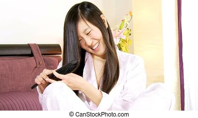 Happy asian girl brushing long hair